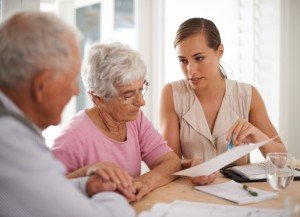 A female business woman explains information to an elderly couple
